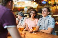 Amis heureux buvant de la bière et parlant à la barre Photographie stock libre de droits