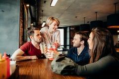 Amis heureux buvant des boissons ayant l'amusement tout en passant le temps ensemble en café Images stock