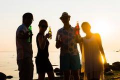 Amis heureux buvant des boissons et ayant une partie Photo libre de droits