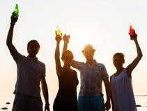 Amis heureux buvant des boissons et ayant une partie Image stock