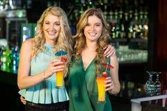 Amis heureux buvant des cocktails Image stock