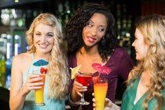 Amis heureux buvant des cocktails Image libre de droits
