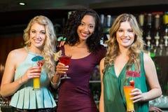 Amis heureux buvant des cocktails Photographie stock libre de droits