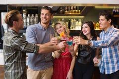Amis heureux buvant des cocktails ensemble Image stock