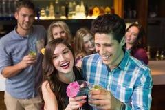 Amis heureux buvant des cocktails ensemble Photographie stock libre de droits