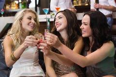Amis heureux buvant des tirs ensemble Images stock
