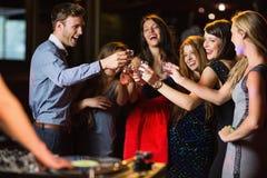 Amis heureux buvant des tirs par la cabine du DJ Photos stock