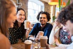 Amis heureux buvant du café au restaurant Photographie stock