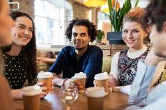 Amis heureux buvant du café au restaurant Image libre de droits