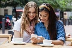 Amis heureux buvant du café tout en à l'aide du téléphone intelligent au café de trottoir Image stock