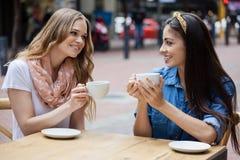 Amis heureux buvant du café tout en se reposant au café de trottoir Images stock