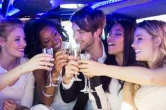 Amis heureux buvant du champagne Photos stock
