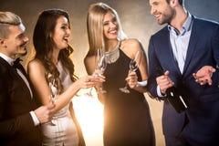 Amis heureux buvant du champagne Photographie stock