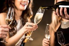 Amis heureux buvant du champagne Image stock