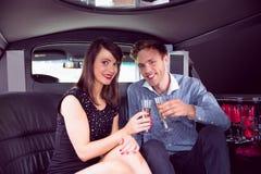 Amis heureux buvant du champagne dans la limousine Images stock