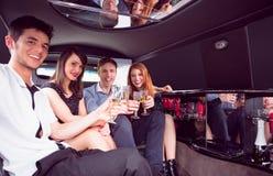 Amis heureux buvant du champagne dans la limousine Photos stock