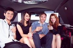 Amis heureux buvant du champagne dans la limousine Image stock