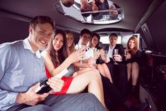 Amis heureux buvant du champagne dans la limousine Image libre de droits