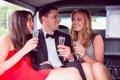 Amis heureux buvant du champagne dans la limousine Photographie stock