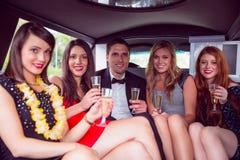 Amis heureux buvant du champagne dans la limousine Photos libres de droits