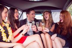 Amis heureux buvant du champagne dans la limousine Photo stock