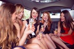 Amis heureux buvant du champagne dans la limousine Photo libre de droits