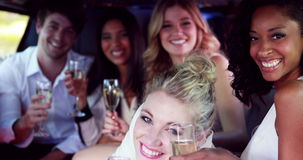 Amis heureux buvant du champagne dans la limousine banque de vidéos