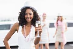 Amis heureux buvant du champagne devant une limousine Images libres de droits
