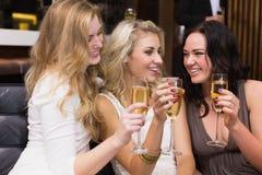 Amis heureux buvant du champagne ensemble Images stock