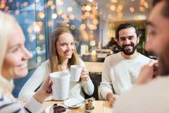 Amis heureux buvant du thé au café Image stock