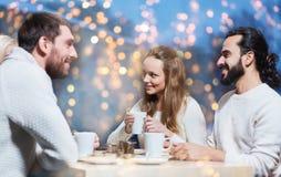 Amis heureux buvant du thé au café Photos stock
