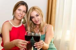 Amis heureux buvant du vin rouge Images stock