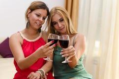 Amis heureux buvant du vin rouge Photos stock