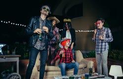 Amis heureux buvant et ayant l'amusement avec des costumes en partie Images libres de droits