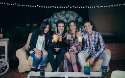 Amis heureux buvant et ayant l'amusement en partie Photo libre de droits