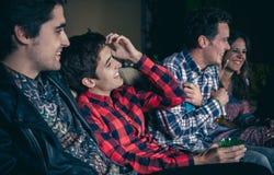 Amis heureux buvant et riant en partie Photographie stock