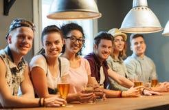 Amis heureux buvant la bière et des cocktails à la barre Photos stock