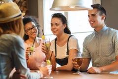 Amis heureux buvant la bière et des cocktails à la barre Images libres de droits