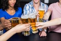 Amis heureux buvant la bière et le grillage Image stock
