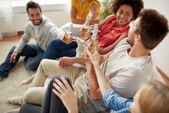 Amis heureux buvant la partie de bière à la maison Images libres de droits