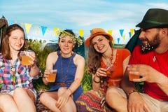 Amis heureux buvant les tentes extérieures au terrain de camping Image stock