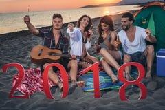 Amis heureux célébrant à la partie de la veille du ` s de nouvelle année de la plage 2018 Photos stock