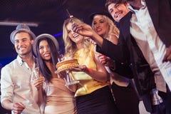 Amis heureux célébrant l'anniversaire avec le gâteau Photo stock