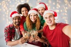 Amis heureux célébrant Noël à la fête au bureau Photographie stock