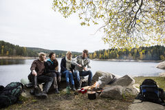 Amis heureux campant sur au bord du lac Photographie stock libre de droits