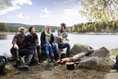 Amis heureux campant sur au bord du lac Photo libre de droits