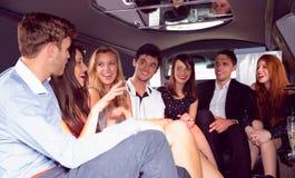 Amis heureux causant dans la limousine Photos libres de droits