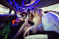 Amis heureux causant dans la limousine Photo libre de droits