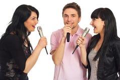 Amis heureux chantant à la réception de karaoke Images stock