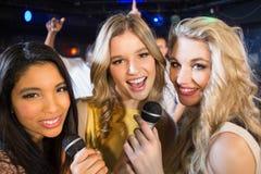 Amis heureux chantant au karaoke Images stock